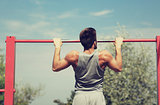 young man exercising on horizontal bar outdoors