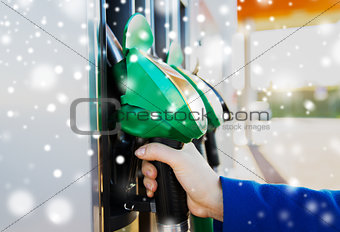 close up of hand holding hose at gas station