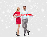 happy couple with red sale sign over snow