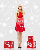 smiling woman with red sale sign over snow