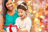 happy mother and girl with gift box over lights