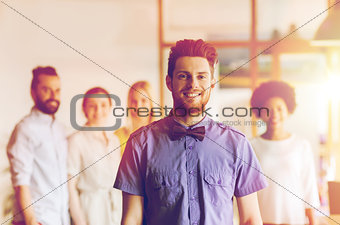 happy young man over creative team in office