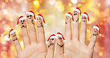 close up of fingers with smiley in santa hats