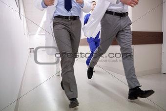 close up of medics or doctors running at hospital