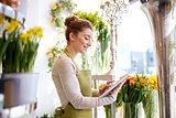 woman with tablet pc computer at flower shop