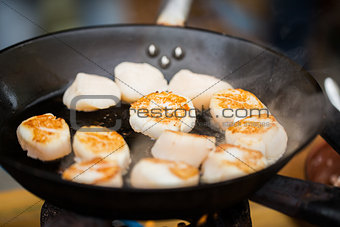 close up of scallops frying in cast iron pan