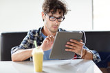 man with tablet pc and earphones sitting at cafe