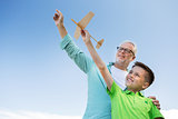 senior man and boy with toy airplane over sky