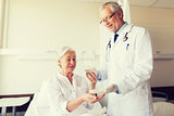 doctor giving medicine to senior woman at hospital