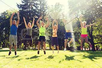 group of happy friends jumping high outdoors