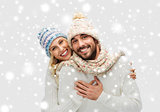 smiling couple in winter clothes hugging over snow