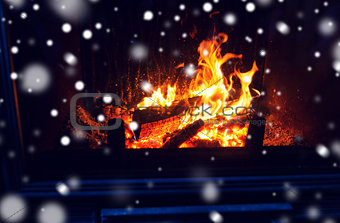 close up of firewood burning in fireplace and snow