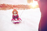parent carrying happy little kid on sled in winter