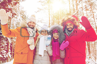 group of friends waving hands in winter forest