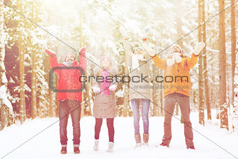 group of happy friends playin with snow in forest