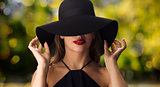 beautiful woman in black hat over dark background