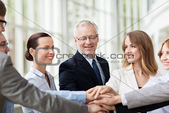 business people putting hands on top in office