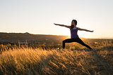 Woman doing yoga warrior II pose during sunset