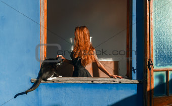 Beautiful girl with red hair and cat at the window