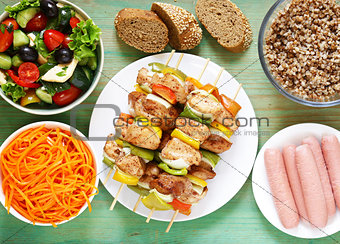 Table served for lunch.Skewers, salads, side dishes and bread. Healthy food.