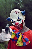 scary evil clown with a gun
