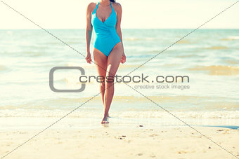 close up of woman in swimsuit walking on beach