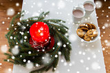 close up of christmas wreath with candle on table