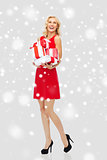 happy woman in red dress holding christmas gifts