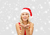happy woman in santa hat holding something on palm