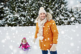 happy man carrying little kid on sled in winter