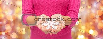 close up of woman in sweater holding snowflake