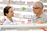 happy pharmacist talking to senior man at pharmacy