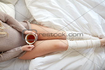 close up of woman with tea cup in bed