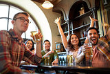 friends with beer watching football at bar or pub