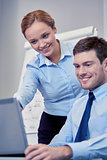 smiling businesspeople with laptop in office