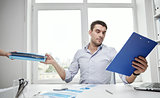 businessman taking papers from secretary in office