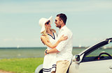 happy man and woman hugging near car at sea