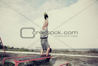 young man exercising on bench outdoors