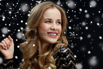 close up of happy young woman dancing over snow