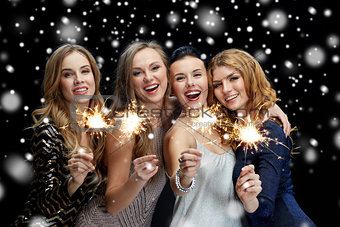 happy young women with sparklers over snow