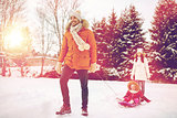 happy family with sled walking in winter outdoors