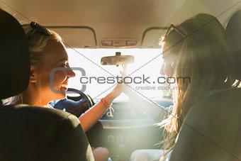 happy teenage girls or women driving in car