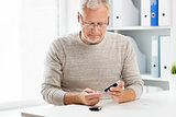senior man with glucometer checking blood sugar