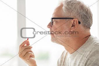close up of senior man taking medicine pill