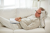 senior man sleeping on sofa with book at home