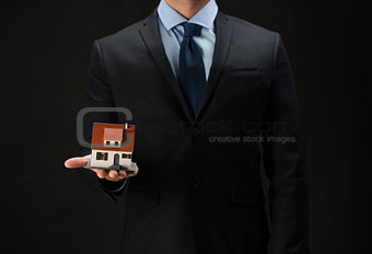close up of businessman holding house model
