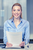 smiling woman holding papers in office