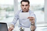 businessman showing blank paper card at office
