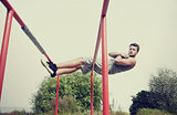 young man doing sit up on parallel bars outdoors