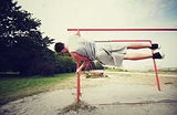 young man exercising on parallel bars outdoors